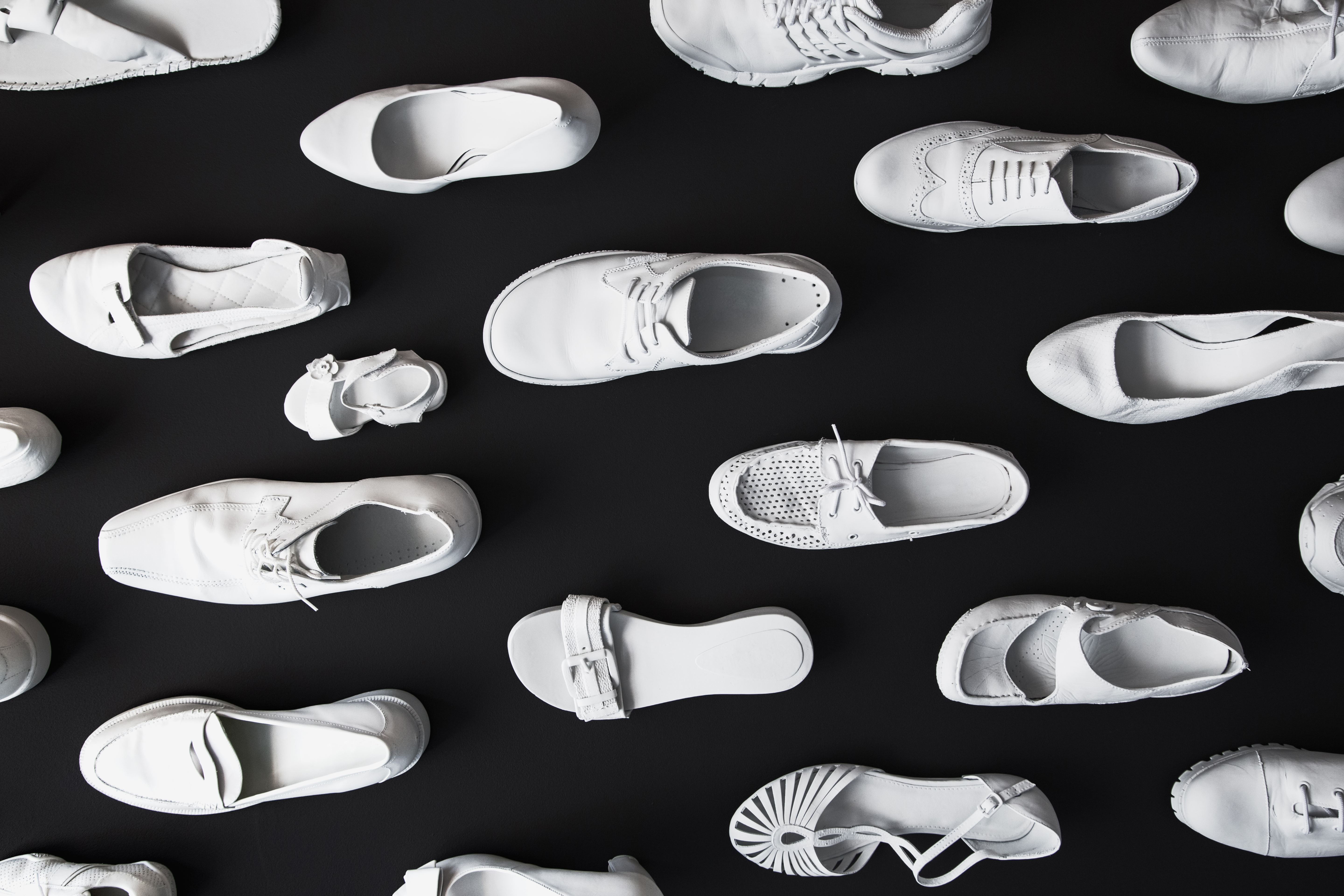 Many different white shoes on a black background