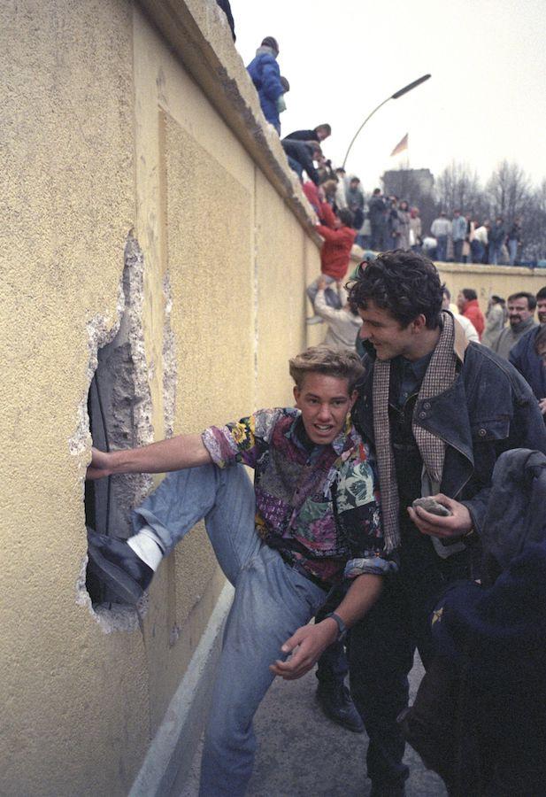 People climbing the Berlin Wall