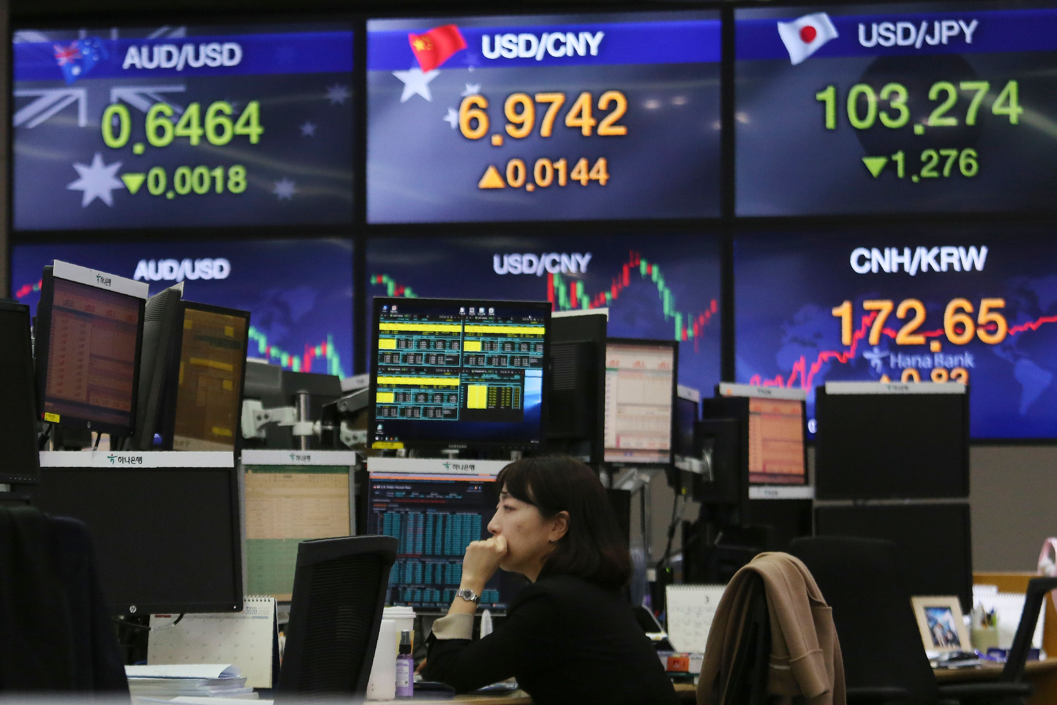 Currency trader watches monitors at the foreign exchange dealing room of the KEB Hana Bank headquarters in Seoul, South Korea, . Asian shares plunged Thursday after the World Health Organization declared a coronavirus pandemic and indexes sank on Wall Street Financial Markets, Seoul, South Korea - 12 Mar 2020