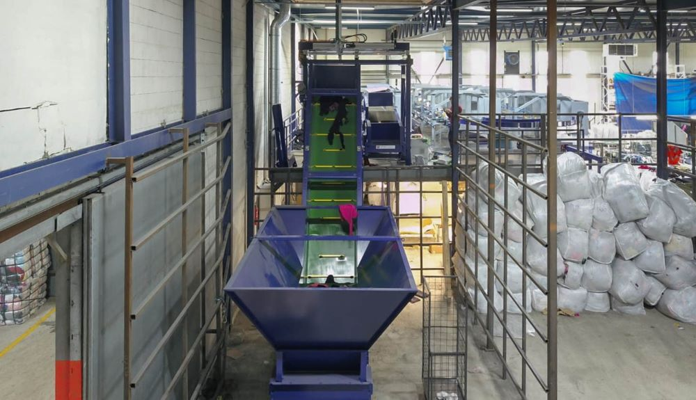 The Fibersort is a machine that automatically sorts large volumes of mixed post-consumer textiles by fiber composition and color.