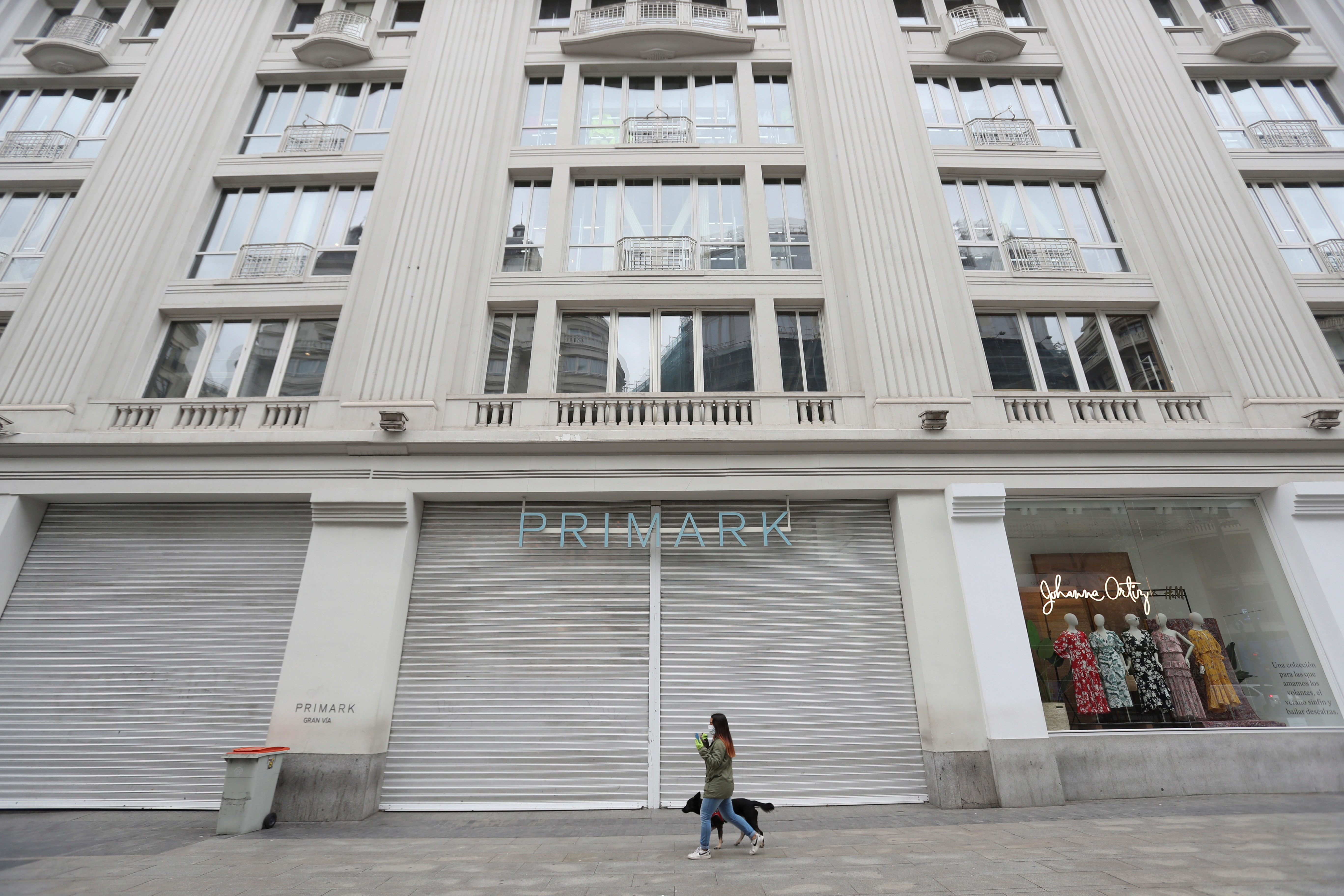 A woman walks her dog past a closed Primark store in downtown Madrid, Spain, 20 March 2020. The pandemic caused an unexpected economic crisis. Spain faces the sixth day of national lockdown on 20 March in an effort to slow down the spread of the pandemic COVID-19 disease. According to the latest figures provided by the health ministry, there are at least 18,074 confirmed coronavirus infections throughout Spain, while 832 people have died so far in the Mediterranean country. Coronavirus crisis, Madrid, Spain - 20 Mar 2020