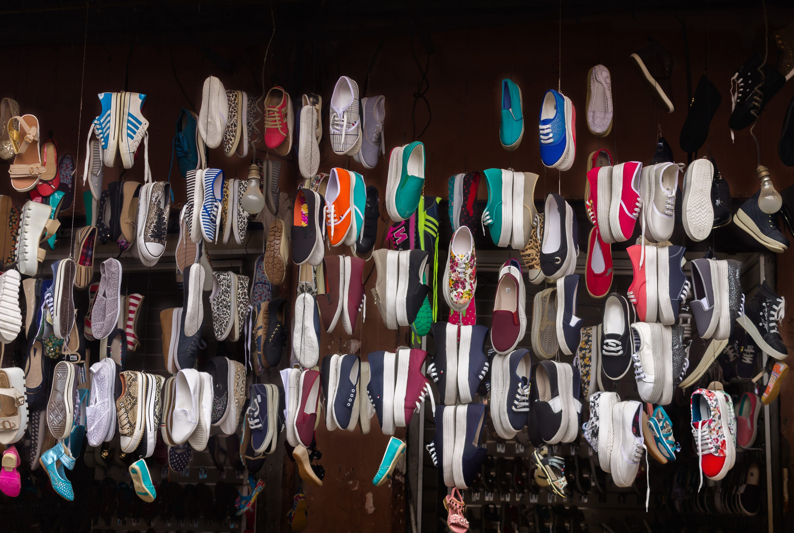 Lots of different shoes hanging on the rope in the showcase of market