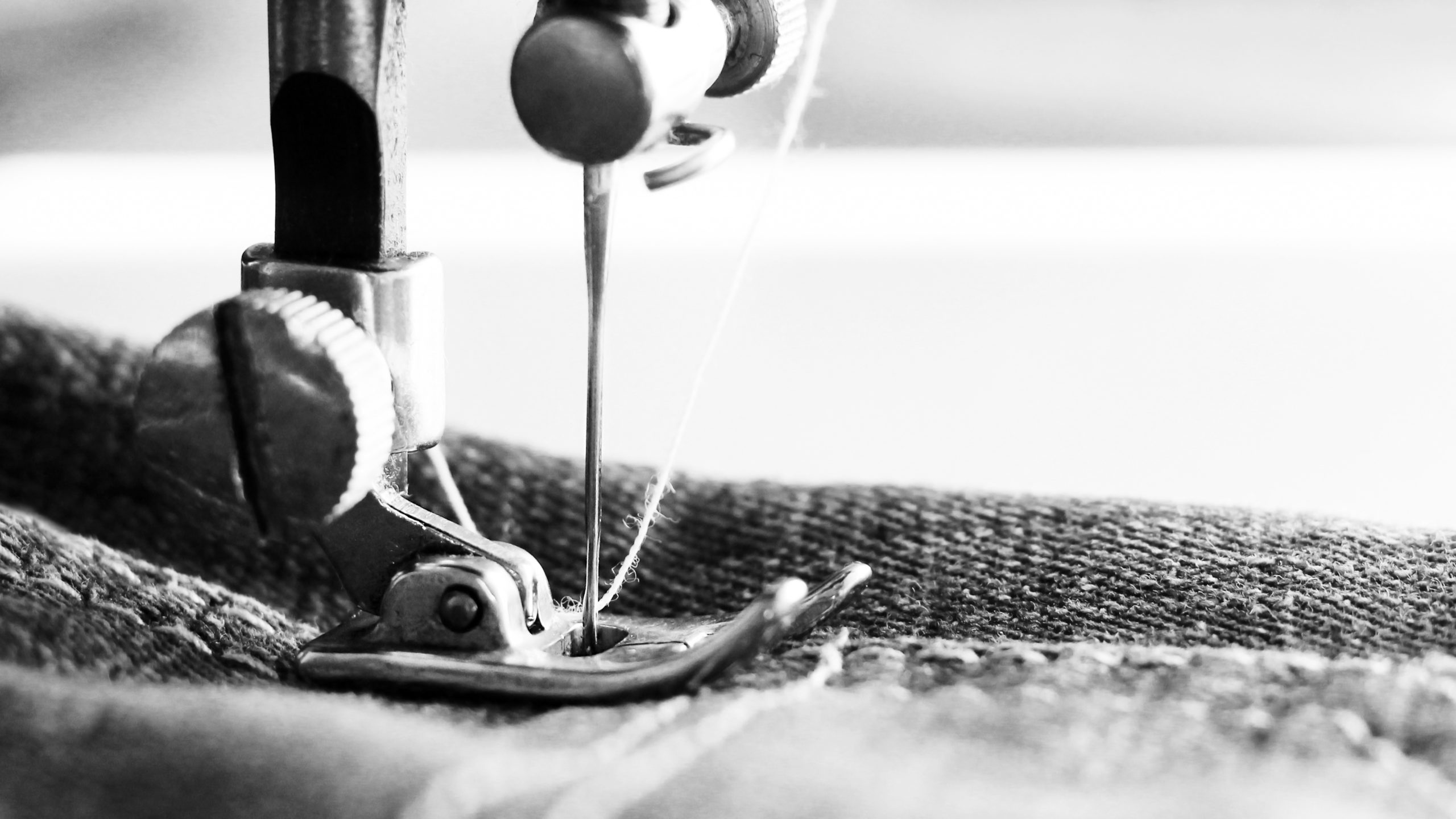 Close-up detail of the sewing machine, jeans