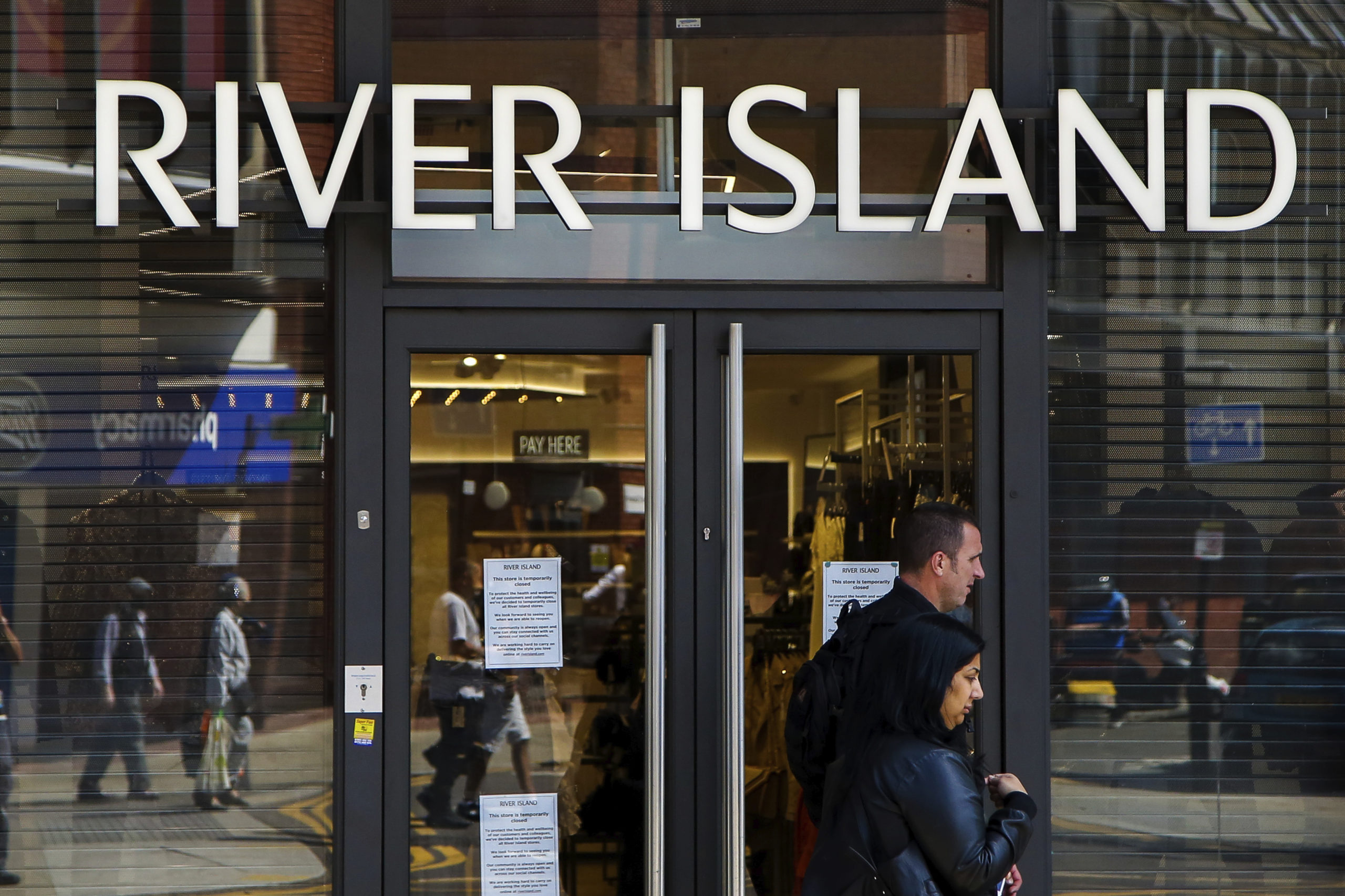Shoppers walk past a River Island store in north London.