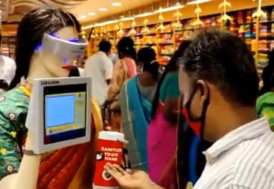 In a Pothys showroom in Madurai, India, a robot mannequin offers a shopper hand sanitizer while wearing one of the company's signature sarees.