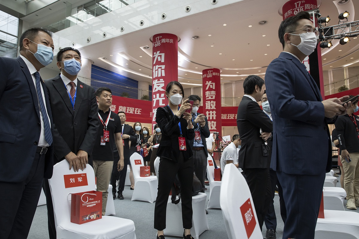 Attendees wear masks to curb the spread of the new coronavirus before the ceremony to mark the listing of JD.com on the Hong Kong Stock Exchange at the JD.com headquarters in Beijing on Thursday, June 18, 2020.