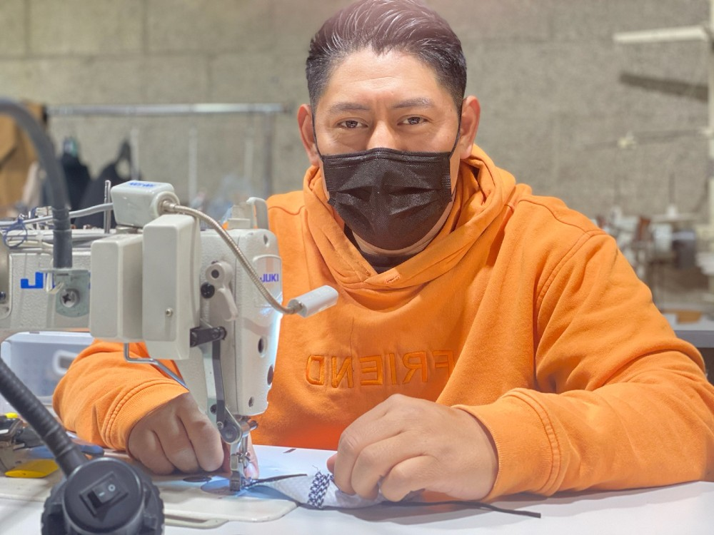 A worker at Los Angeles-based Lefty Production Co. sews a mask.
