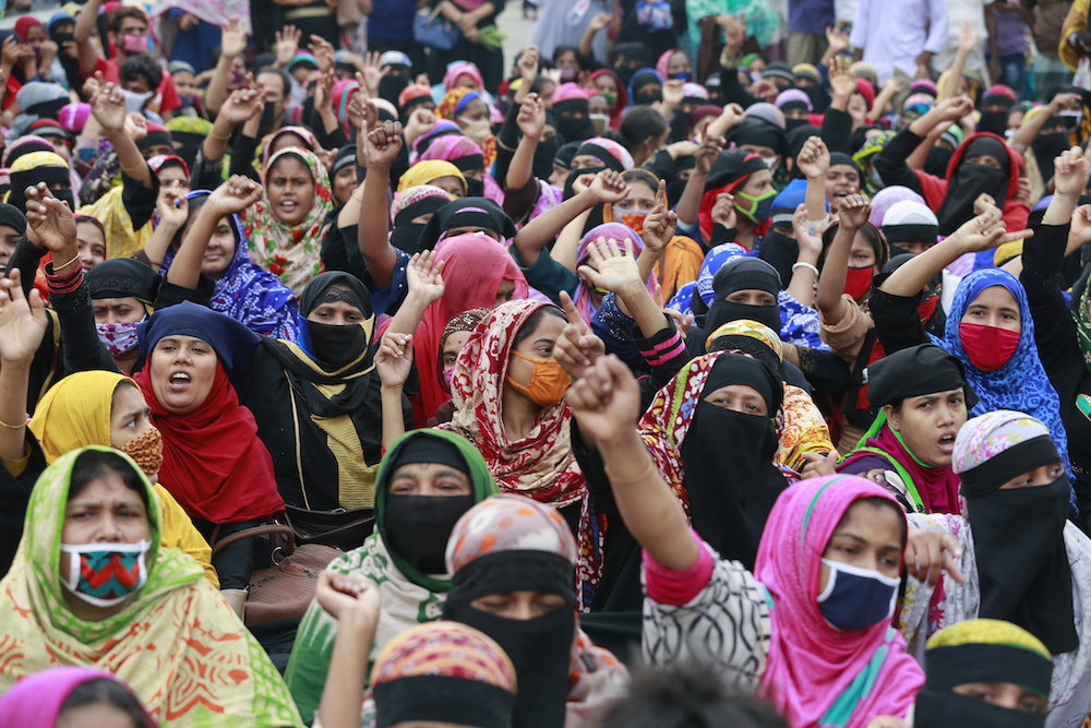 Bangladeshi garment workers block a road as they gather in a protest demanding their unpaid wages during nationwide lockdown to curb the spread of coronavirus in Dhaka, Bangladesh