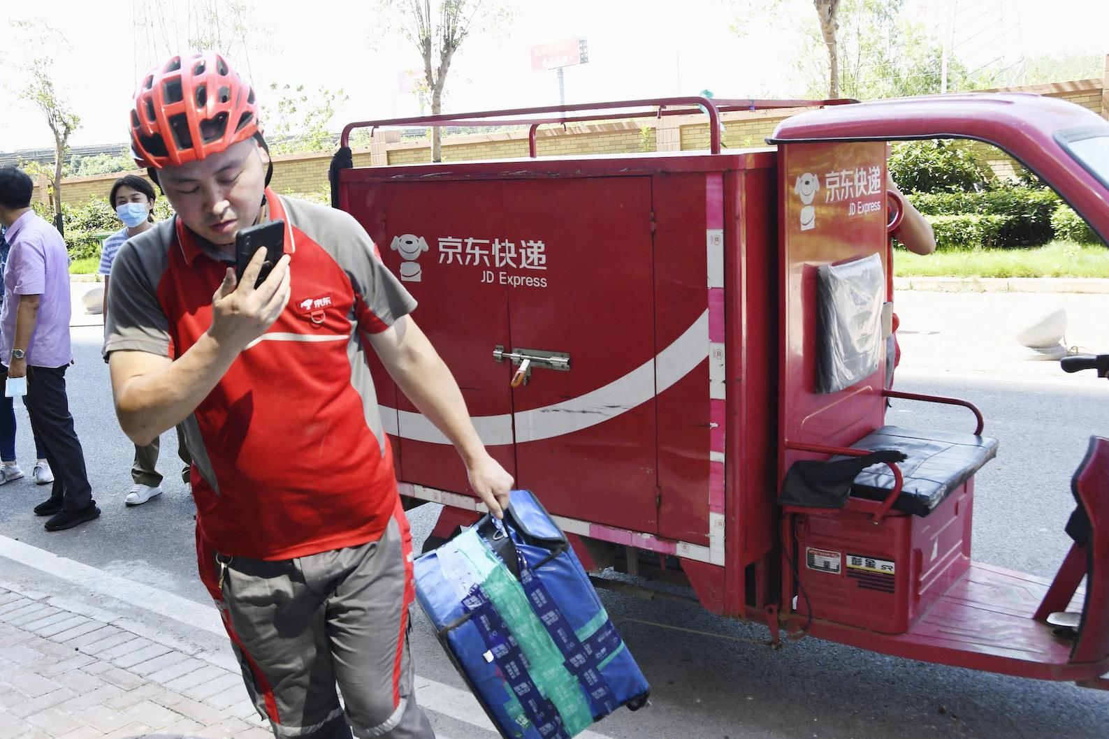 A JD.com Inc. worker makes a delivery to an apartment building in Wuhan, China, on Aug. 13, 2020.