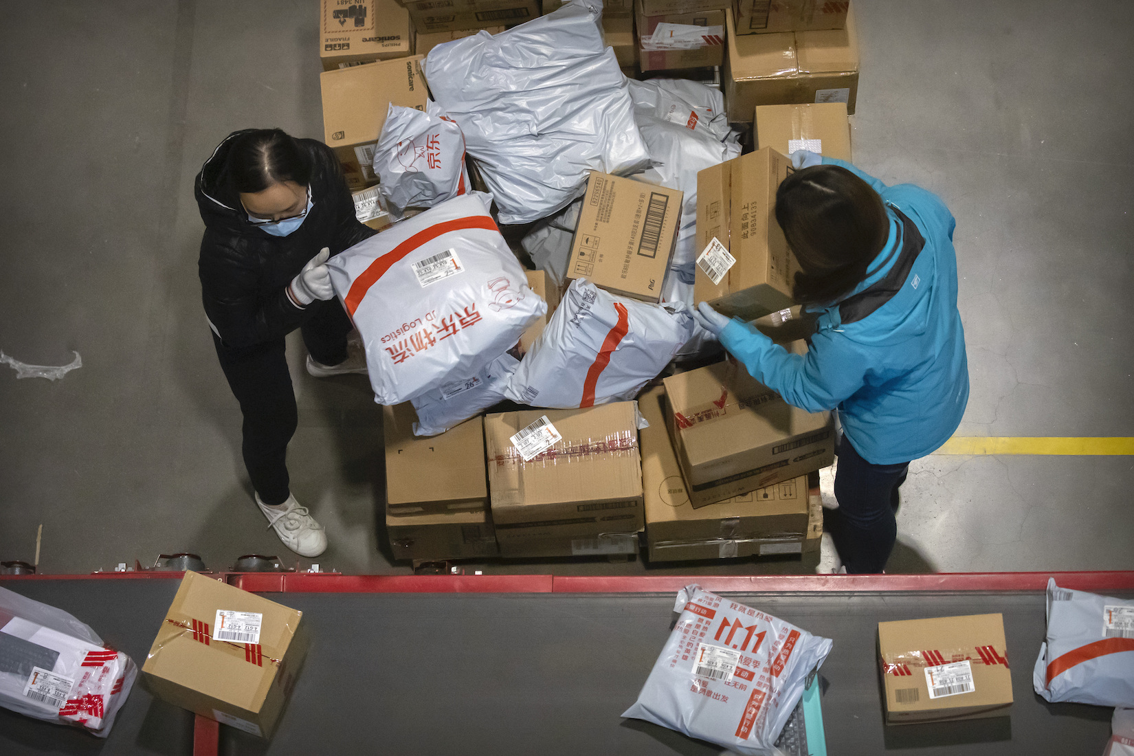 Workers load parcels onto a conveyor belt at a JD.com warehouse in Beijing, Wednesday, Nov. 11, 2020.