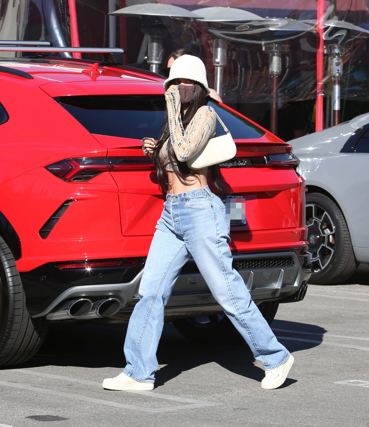 Kylie Jenner sports a crop-top and loose-fitting denim jeans.