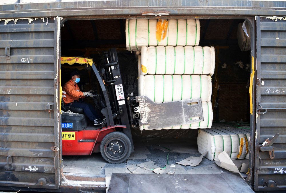 A forklift driver moves lint cotton produced in Xinjiang off a train at a railway freight station in Jiujiang in central China's Jiangxi province Friday, March 26, 2021.