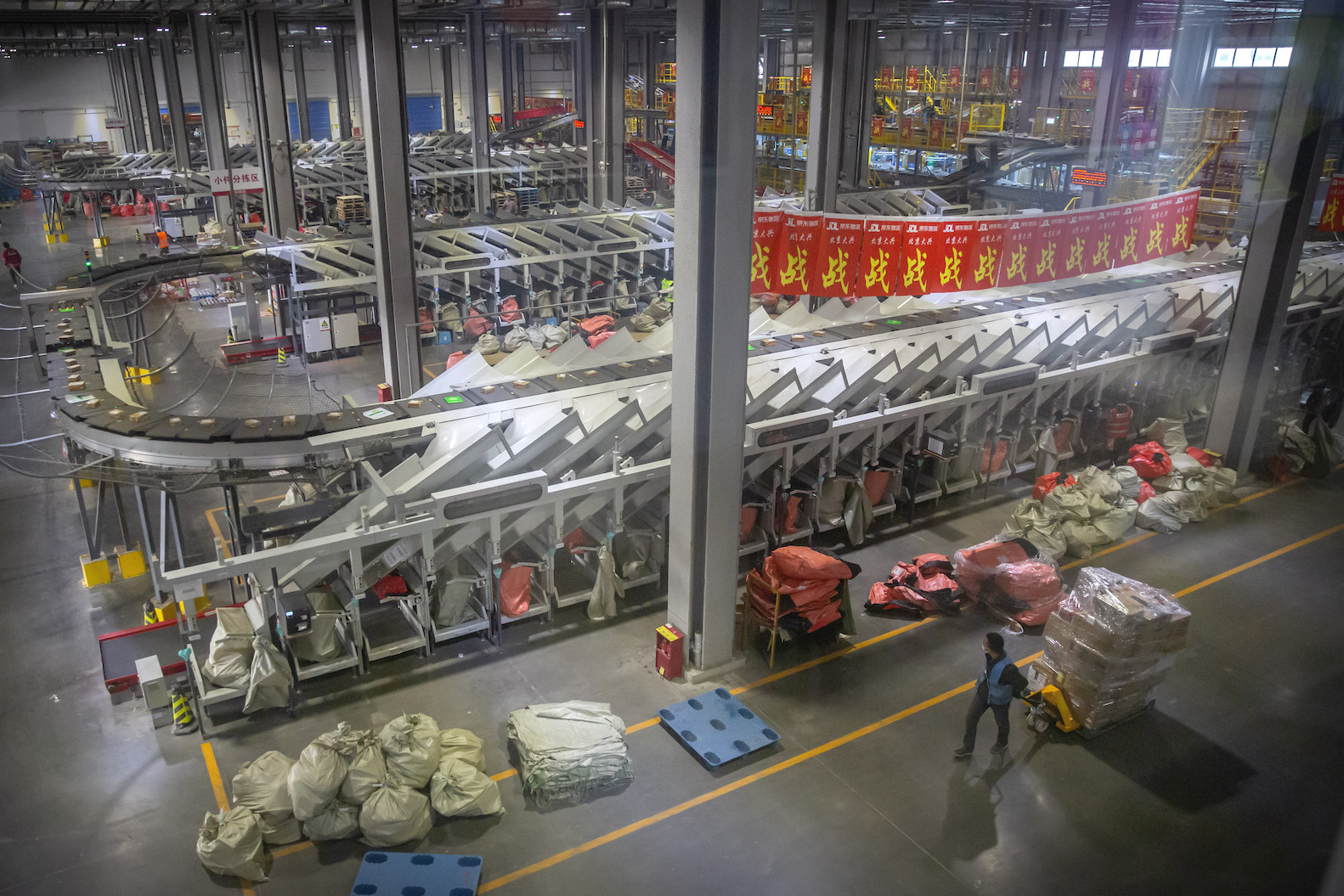 An employee walks past an automated parcel sorting machine at a warehouse for online retailer JD.com in Beijing, Wednesday, Nov. 11, 2020.