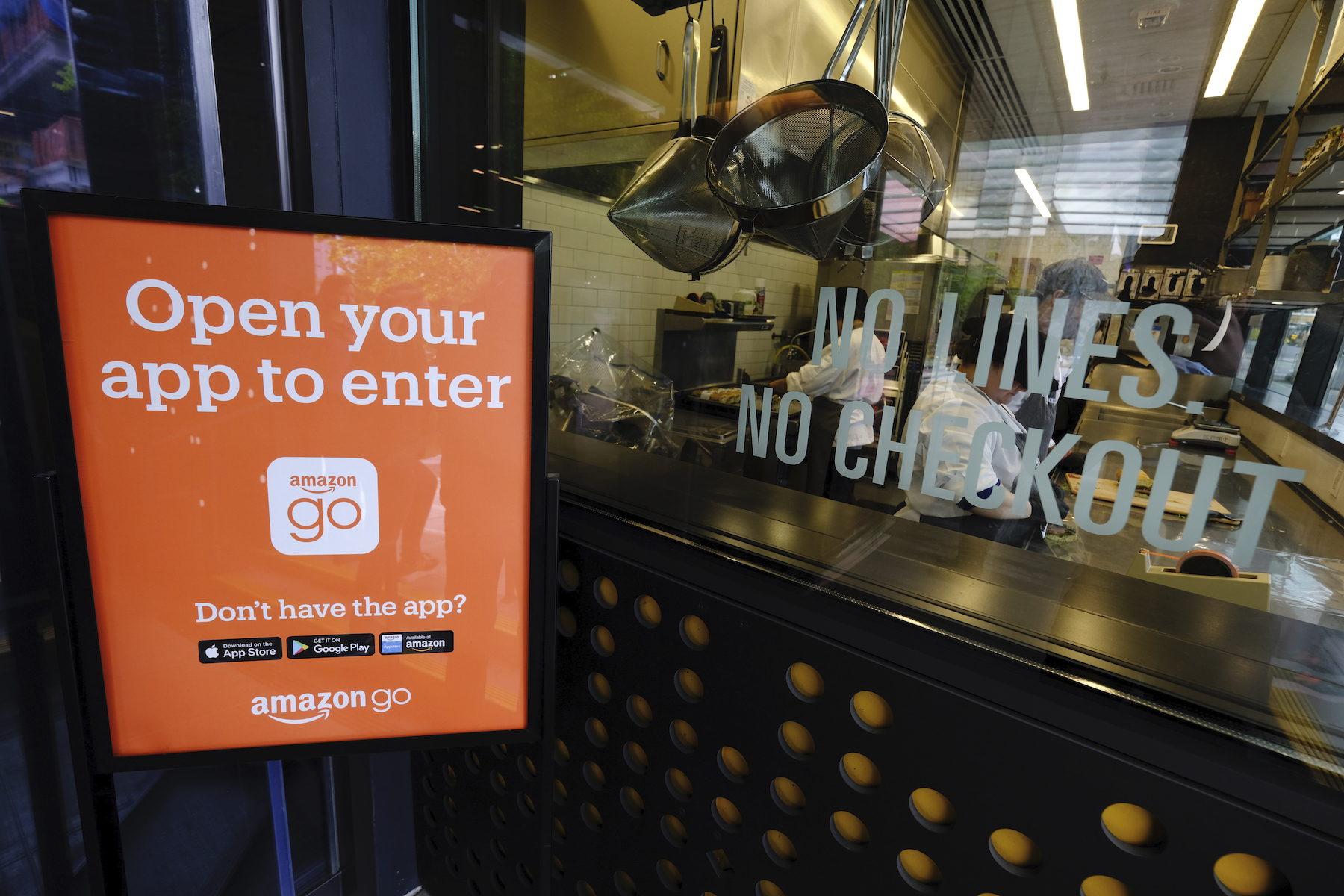Employees make ready-to-eat food at the original Amazon Go convenience store in Seattle.