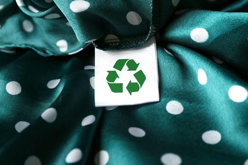 Clothing label with recycling symbol on green garment, closeup